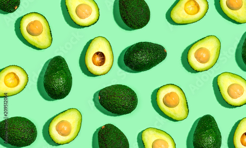 Papel de parede Fresh avocado pattern on a green background flat lay