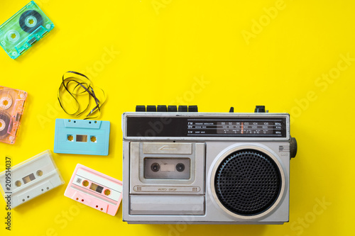 Photographie vintage radio and cassette player on yellow background, flat lay, top view