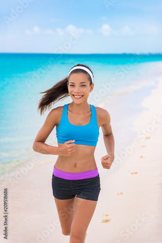 a84ad32906ae Fitness girl running on beach in fashion activewear clothes. happy Asian  woman jogging with blue sports bra and shorts on morning training outside.