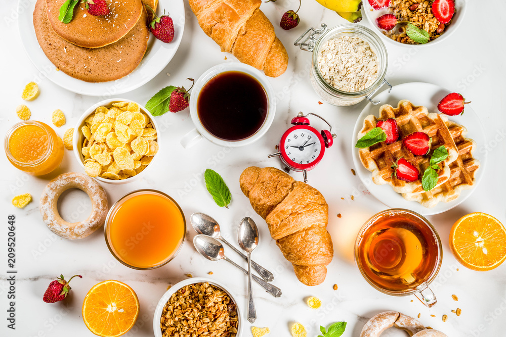 Fototapeta Healthy breakfast eating concept, various morning food - pancakes, waffles, croissant oatmeal sandwich and granola with yogurt, fruit, berries, coffee, tea, orange juice, white background
