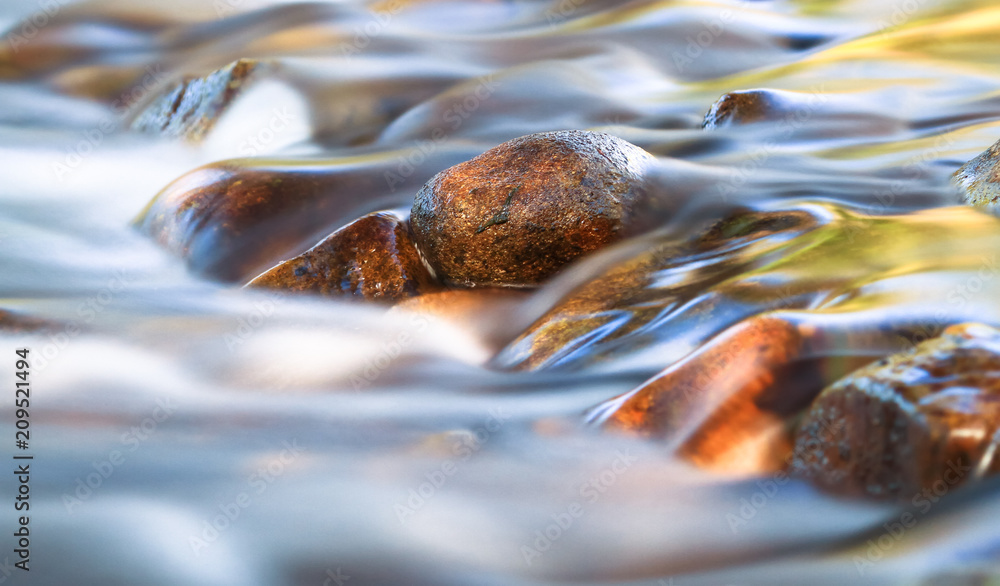 Fototapeta Long exposure of a small stream gently flowing over rounded rocks in the Cathedral Range State Park, Victoria, Australia.