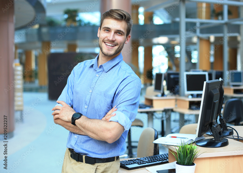 Fototapeta Young man posing confident and positive in professional workplace office with space.