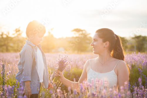 Spoed Foto op Canvas Natuur beautiful mother with wild flowers bouquet and little son look each other loving in summer lavender field