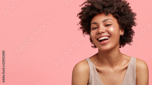 Cute joyful female teenager has broad smile, sparkles on face, prepares to go on disco with friends, being in high spirit, has bare shoulders, stands against pink background, blank space for your text