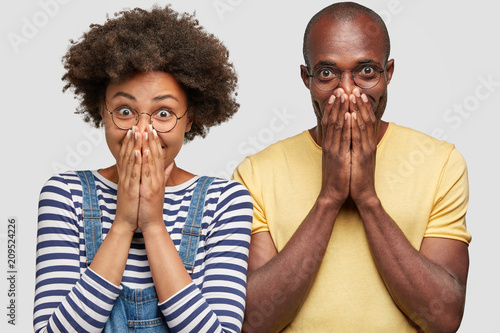 Fotografie, Obraz  Two companions laugh at good joke, giggle happily, cover mouth with hands, pose against white background, have joyful expressions, hear funny stories from interlocutor