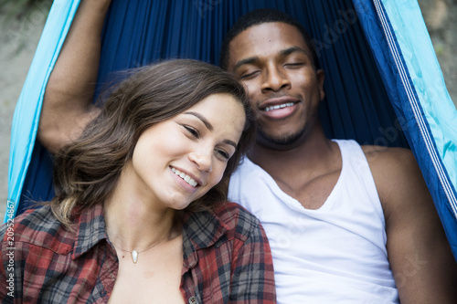 Foto  Mixed race couple laying down in hammock