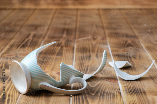 A broken vintage porcelain cup on a wooden table (top view)