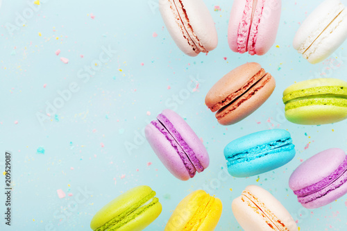 Flying cake macaron or macaroon on blue pastel background. Colorful almond cookies on dessert.