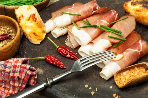 Thinly sliced German black forest ham with sliced ciabatta bread. Sliced and smoked ham with schwarzwald ham or prosciutto. Traditional German food.