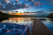 Boat dock. Sunset over the lake. Wooden pier on the lake. Pier on the background of sunset.