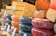 Variety And Different Types Of Cheese On Stall Market Shop Counter. Lot Of Stack Cheese In Store With Blank Label.