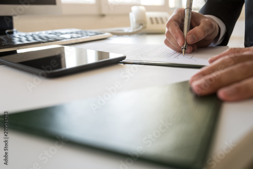 Fotografía  Businessman signing document at his office table in a low angle view