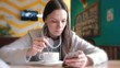 Woman is drinking a hot chocolate with spoon and look on the screen of mobile phone sitting in cafe.