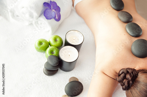 Garden Poster Spa Stone treatment. Top view of beautiful young woman lying on front with spa stones on her back. Beauty treatment concept.