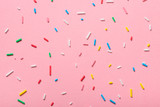 colorful sprinkles over pink background, decoration for cake and bakery