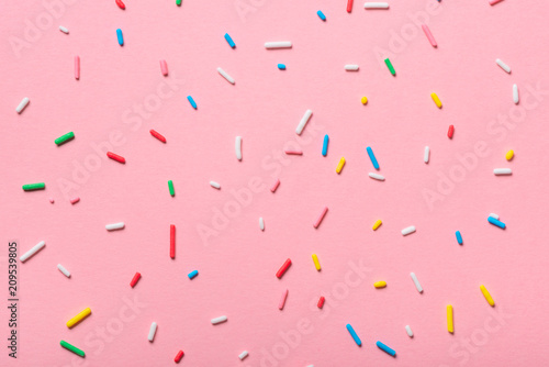 Canvas-taulu colorful sprinkles over pink background, decoration for cake and bakery