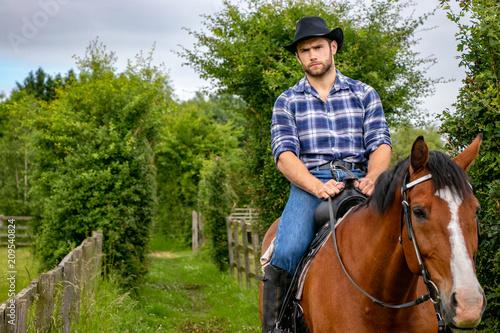 Valokuva Handsome cowboy, horse rider on saddle, horseback and boots