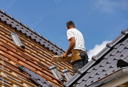 Handwerk - Dachdecker beim Eindecken eines Wohnhauses Fotobehang