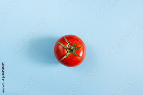 One red ripe tomato in the center of blue background.