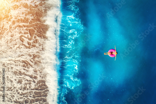 Fotografía  Aerial view of woman swimming on the pink swim ring in the transparent sea and beautiful waves in Europe