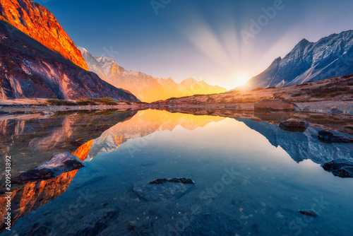 Canvas Prints Mountains Beautiful landscape with high mountains with illuminated peaks, stones in mountain lake, reflection, blue sky and yellow sunlight in sunrise. Nepal. Amazing scene with Himalayan mountains. Himalayas