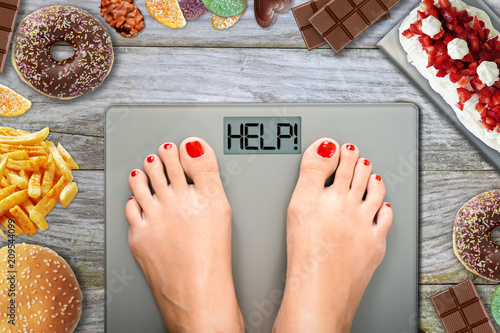 Junk food or sugar sweets temptations when you diet concept with woman feet on w Canvas Print