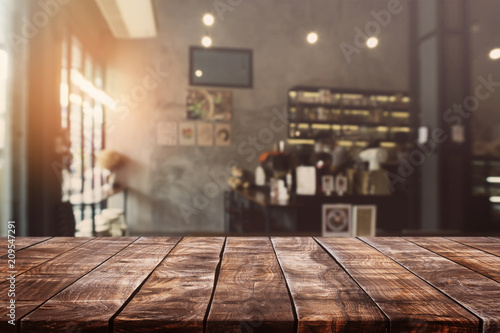 Fototapeta Empty old wood table top and blurred bokeh cafe and coffee shop interior background with vintage filter - can used for display or montage your products. obraz