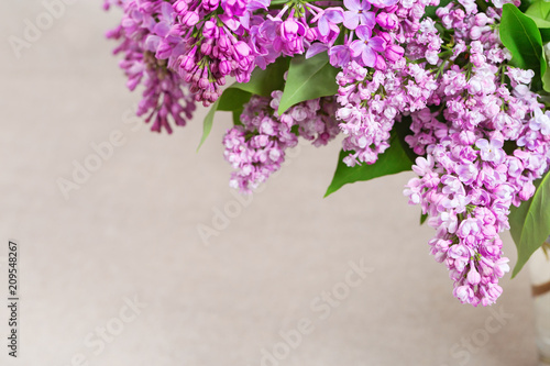 Foto op Canvas Lilac Branches of a blossoming lilac close-up on a blurred cloth background with copy space. Selective focus.