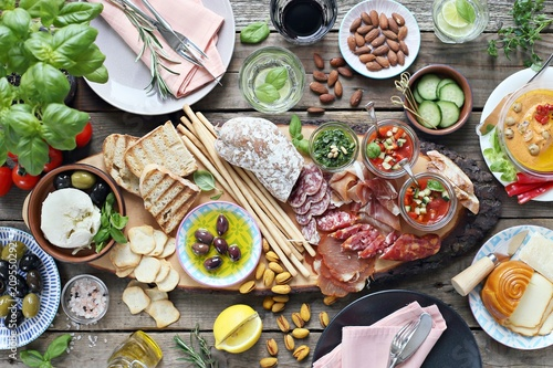 Spoed Fotobehang Voorgerecht Mediterranean appetizers table concept. Dinner table with tapas selection: cured meat and salami, gazpacho soup, jamon, olives, cheese, hummus and vegetables. Overhead view.