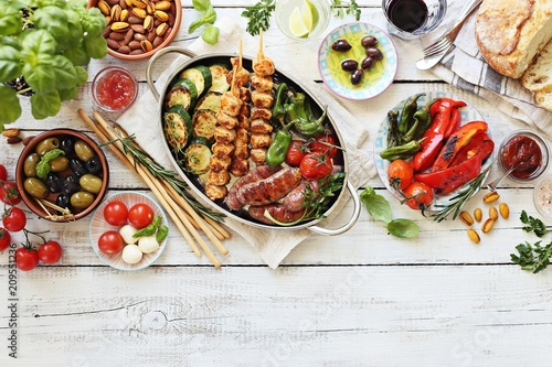 Grilled meat, chicken skewers and sausage  with roasted vegetables and appetizers variety serving on party outdoor table Canvas Print