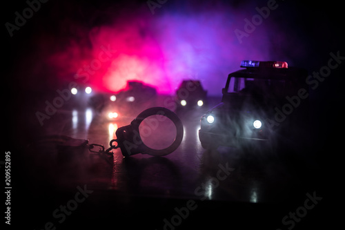 Closed handcuffs on the street pavement at night with police car lights Fototapeta
