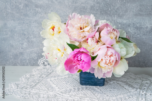 Bouquet of peony flowers in blue flower pot. Copy space, holiday background