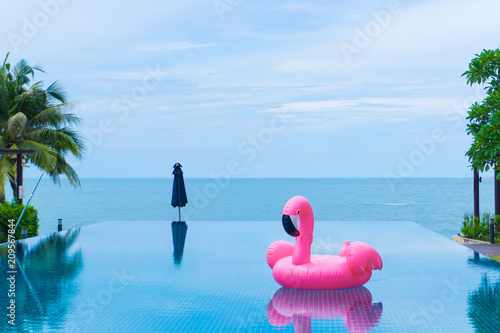 flamingo raft floating in swimming pool in front of the sea and island