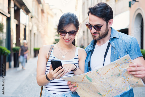 Stampa su Tela Young happy tourist couple visiting travel destination city with smartphone app