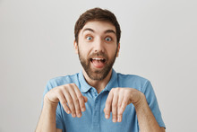 Friends Say His Girlfriend Tamed Him Like Dog. Funny European Boyfriend With Beard Making Dumb Face, Sticking Out Tongue And Standing With Folded Hands Over Gray Wall As If He Is Puppy
