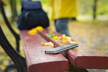 Forgotten Smartphone On A Park Bench. Woman Is Leaving From A Bench Where She Lost Her Cell Phone.
