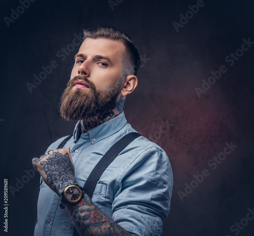 Fototapeta Portrait of a handsome old-fashioned hipster in a blue shirt and suspenders. obraz