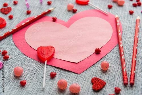Photo Flat lay arrangement of pink and red paper heart lying on table with red pencils