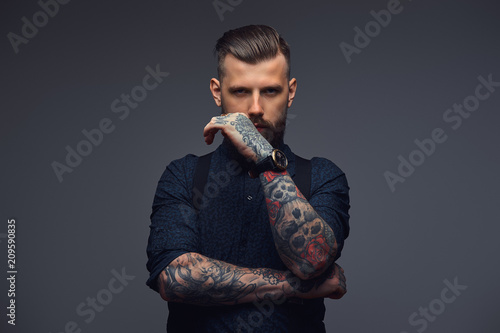 Pensive handsome old-fashioned hipster in shirt and suspenders, pose with hand on chin Wallpaper Mural