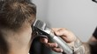 Tattoed barber makes haircut for customer at the barber shop by using hairclipper, man's haircut and shaving at the hairdresser, barber shop