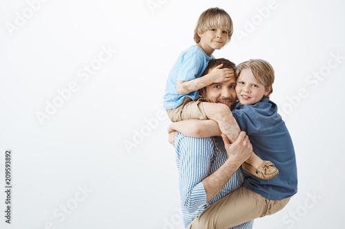 Fotografía  Indoor shot of positive happy family guy holding son with vitiligo on shoulders