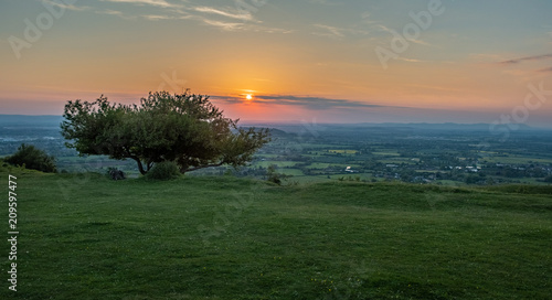 Valokuva  View of sunset from Crickley hill Gloucestershire with  a tree on the edge of the hillside in the foreground