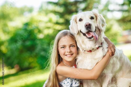 Little girl sitting on the grass with golden retriever dog in the summer park Fototapeta