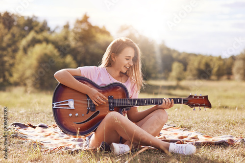 Beautiful young smiling female plays acoustic guitar, sits cross legs on green grass, being in good mood, learns new song, has appealing appearance. People, talent, youth and recreation concept