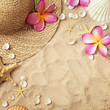 summer background, summer hat, seashells and tropical flowers on sand beach. frame with copy space