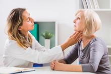 Female Doctor Examines Her Senior Patient's Throat In Office.