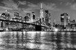 New York City, financial district in lower Manhattan with Brooklin Bridge at night, USA. BW