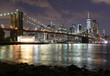 New York City, financial district in lower Manhattan with Brooklin Bridge at night, USA