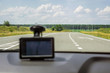 road through the windshield against the background of a blurry navigator indicating the way to the driver