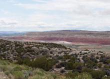 The Shoshone River Near The Bighorn Canyon Winding Through A Valley Lined By Red Rock Cliffs.